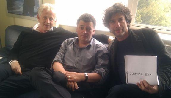 Richard Curtis, Stephen Moffat e Neil Gaiman com um roteiro na mão.