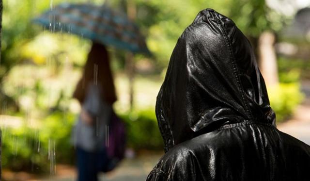 O assassino observa uma vítima na chuva