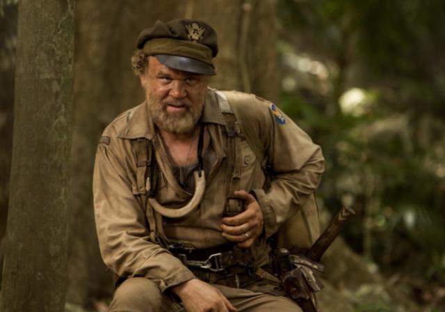 John C. Reilly sentado na floresta