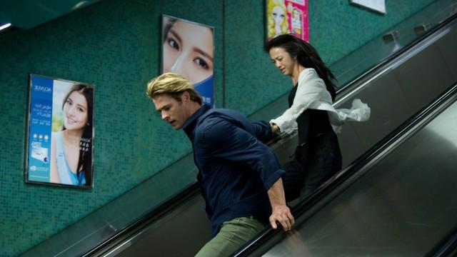 casal de protagonistas correm em escada rolante