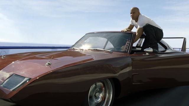 Vin Diesel em pé no carro em movimento