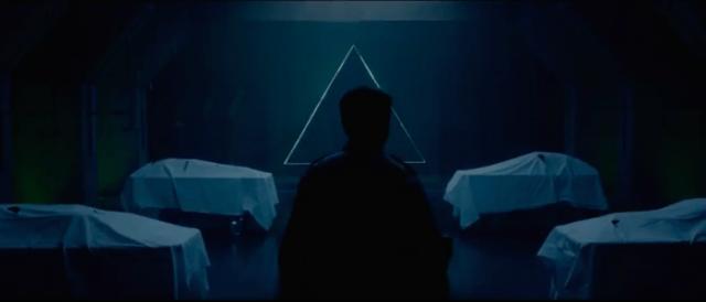homem caminha para triângulo em parede no necrotério