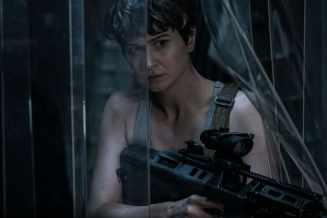 Katherine Waterstone com arma em momento sombrio
