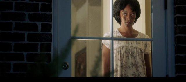 mulher vesga diante da janela