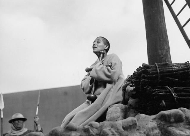 Joana D'Arc abraça cruz diante da fogueira