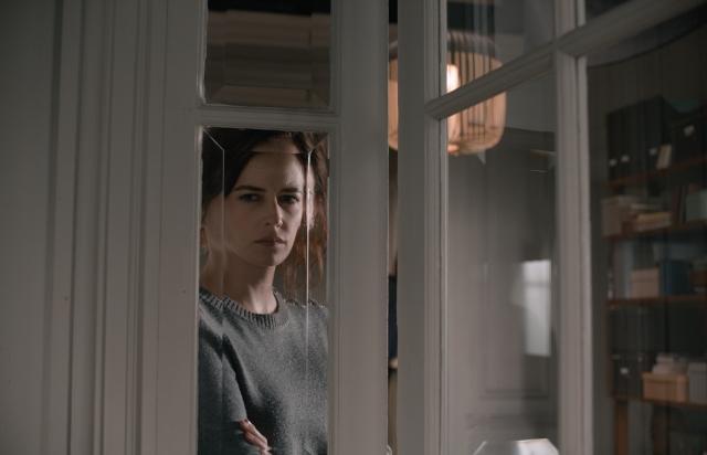 Elle observa pelo vidro da porta