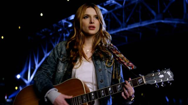 Katie com um violão e uma ponte no fundo