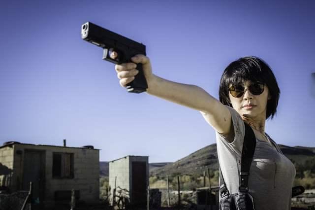 Lin faz pose heróica enquanto mira com arma